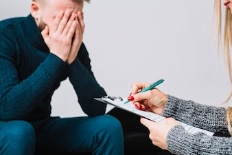 Close-up of female psychologist with male depressed client taking notes