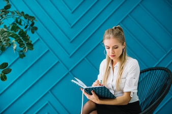 Close-up of female psychologist writing notes in diary sitting against blue wall
