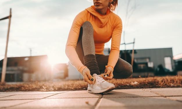 Крупным планом женщина бегун на коленях и связывать шнурки на улице в солнечный день