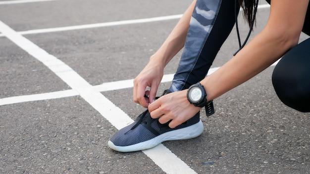 彼女の靴をひもで締める女性ランナーのクローズアップ。