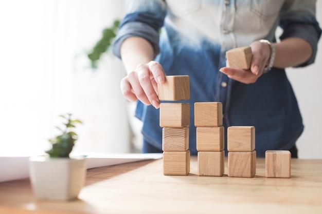 Конец-вверх руки женщины штабелируя деревянный блок на таблице на офисе
