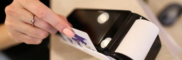 プラスチック製のクレジットカードとターミナルサーバーを使用して支払いを行う女性の売り手のクローズアップ。ショッピングストアでのキャッシュレスペイの簡単な方法。現代の技術コンセプト