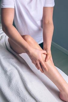 臨床センターで女性の脚にリンパドレナージマッサージをしている女性セラピストの手のクローズアップ。医学、ヘルスケア、美容のコンセプト。