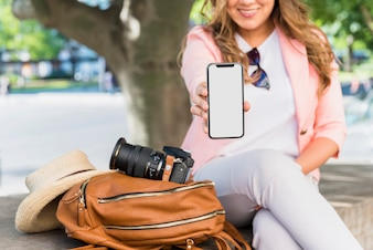 Close-up of female tourist sitting beside the bag; hat and camera showing her mobile phone display