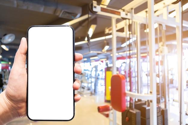 女性の使用のクローズアップスマートフォンのぼやけた画像を保持している手の焦点がぼけたスポーツジムのインテリアとスポーツエクササイズ機器を備えたフィットネスヘルスクラブの抽象的なぼかしジムのぼかしの背景。