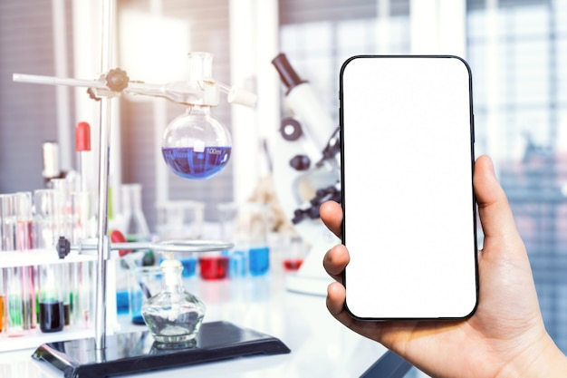 Крупный план женского смартфона с размытыми изображениями с микроскопом и пробирками с лабораторной посудой в лабораторных условиях, исследования и научная концепция