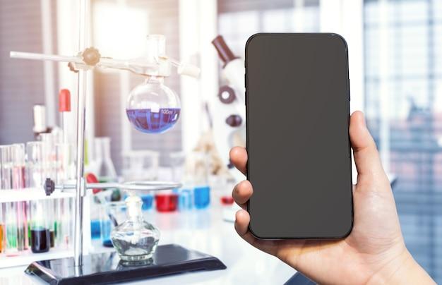 실험실 배경, 연구 및 과학 개념에서 실험실 유리 제품이 있는 현미경 및 테스트 튜브로 여성이 스마트폰을 사용하는 흐릿한 이미지를 클로즈업
