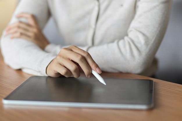 나무 책상에 스타일러스 펜으로 태블릿을 사용하는 여성 클로즈업