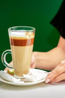 女性ウェイターのクローズアップは、テーブルの上のプレートにキャンディーとコーヒーラテのカップを与えます