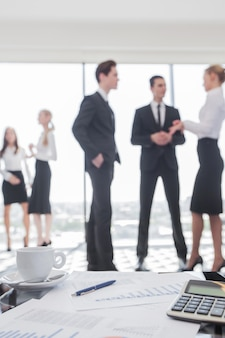 財務報告と計算機のクローズアップ、バックグラウンドで立っているビジネスマンチーム