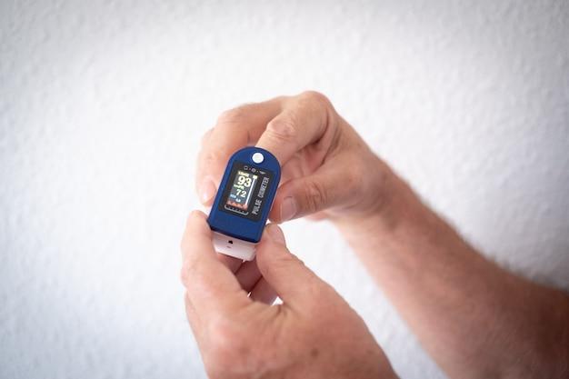 パルスオキシメータデバイスの指と男性の手のクローズアップ。白い背景のパルスオキシメータ。
