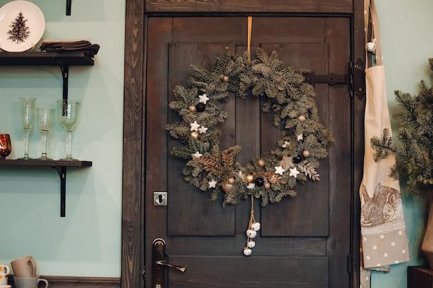 집의 어두운 갈색 나무 정문에 매달려 장식 전나무 나무 크리스마스 화 환의 클로즈업. 정문에 크리스마스 화환을 장식했습니다.