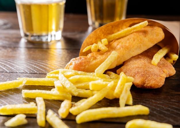 Крупный план рыбы с жареным картофелем в бумажном конусе