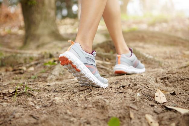 森林歩道で実行中のランニングシューズを身に着けている若い運動女性のフィット脚のクローズアップ。深刻なマラソンの準備をして、屋外で運動する女性ランナーの背面図。