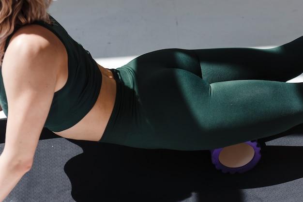 아침 운동 후 근육을 이완시키기 위해 폼 롤러를 사용하여 녹색 스포츠 의류를 입은 피트니스 여성의 클로즈업. 하얀 방에서 다리 마사지를 하는 어린 소녀.