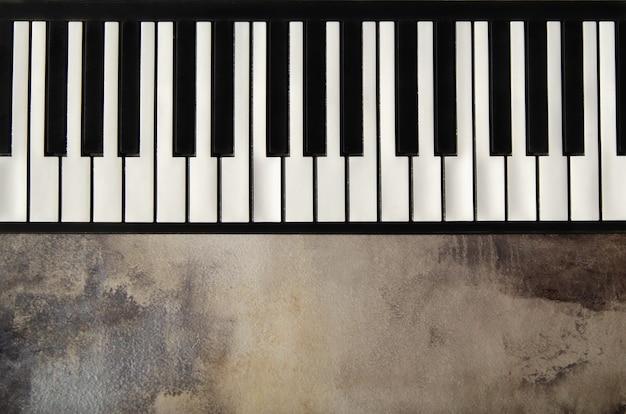 フラットピアノキーボードのクローズアップ、上面図。テクスチャードコンクリートの背景にピアノの鍵盤。