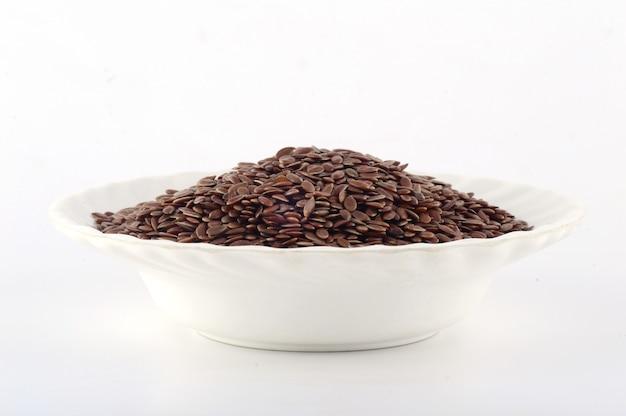 Закройте семена льна в белой тарелке, изолированные на белой поверхности
