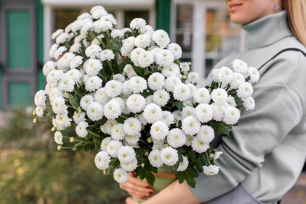 花屋で束を保持している花屋の女性のクローズアップ。