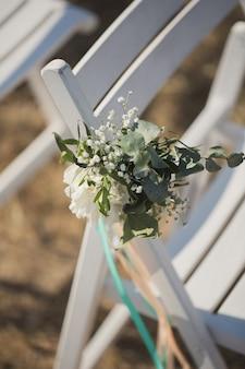 結婚式の椅子に飾られた花のクローズアップ