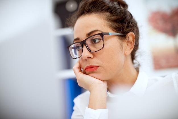 Закройте сосредоточенных профессиональных скучающих деловой женщины, работающей на ноутбуке в офисе.