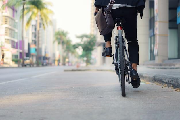 足のクローズアップビジネスマンは彼の朝の通勤のために街の通りで自転車に乗っています。エコ輸送コンセプト。