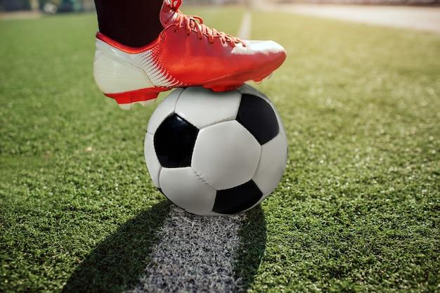 Закройте ноги футболиста в кроссовки socker. он держит это на мяче. мяч стоять на белой линии окрашены на газоне.