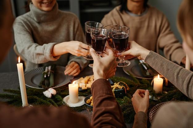 Крупным планом четырех друзей, наслаждающихся рождественским ужином вместе и тостов с бокалами, сидя ...