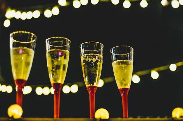 새해를 축하할 준비가 된 새해 밤 샴페인과 함께 4개의 잔을 닫습니다 - 밤과 어두운 배경