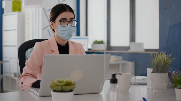 保護フェイスマスクを着用しながらビジネス統計を分析する同僚と話しているフリーランサーのクローズアップ。新しい通常のオフィスに座っているチームは、コロナウイルスのパンデミックの間に社会的距離を維持します