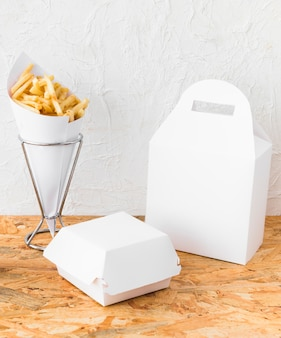 Close-up of french fries and food parcel mock up on wooden desk