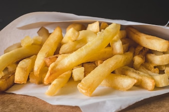 Close up of French fries on wooden table.