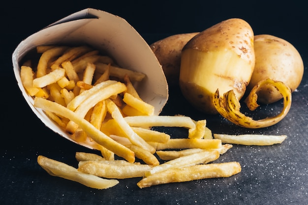 Закройте картофель фри с сырым картофелем на черном фоне.