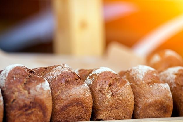 Крупный план свежего черного хлеба в пекарне, свежие буханки