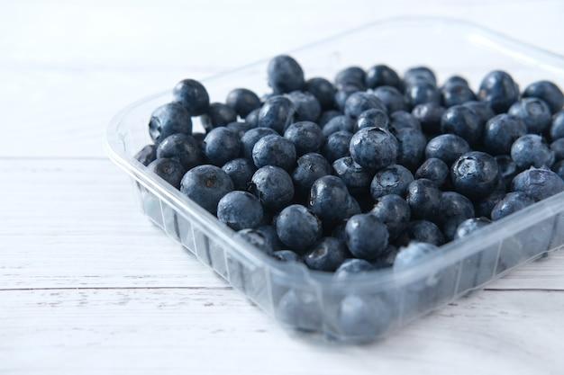 Крупным планом свежие голубые ягоды в пластиковом контейнере на столе
