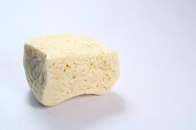 Крупным планом свежего сыра на белом фоне.