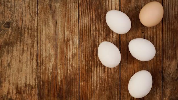 복사 공간이 있는 자연 나무 테이블에 신선한 닭고기 달걀을 닫습니다. 흰 계란과 갈색