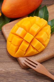 Крупным планом свежего нарезанного манго с зелеными листьями