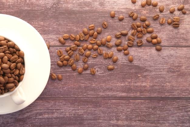 복사 공간이 검은 표면에 컵에 신선한 커피 콩의 닫습니다
