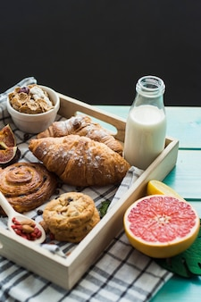 Close-up of fresh croissant; backed cookies; milk; muesli; and citrus fruit with cloth in wooden container