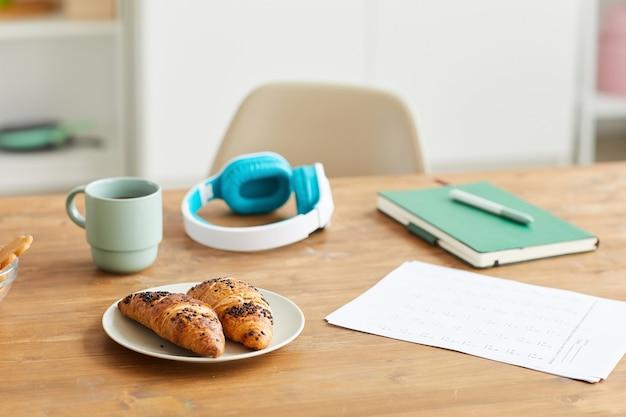Крупным планом свежие круассаны на тарелке с кофе во время перерыва на кофе после учебы