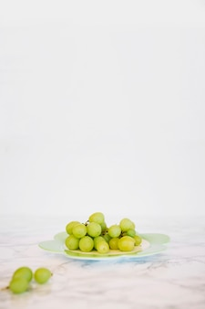 Close-up of fresh green grapes on marble