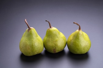 Close up of fresh green pears over black background