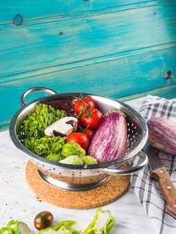 Конец-вверх свежих здоровых овощей в дуршлаге над мраморным столом