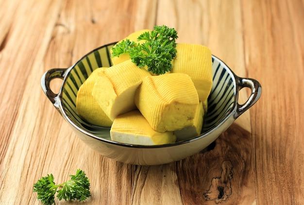 木製テーブル(タフススレンバン)の作りたての生豆腐黄色バンドン豆腐カッティングキューブのクローズアップ。ビーガンヘルシーミールのコンセプト。広告、テキスト、またはレシピ用のコピースペース