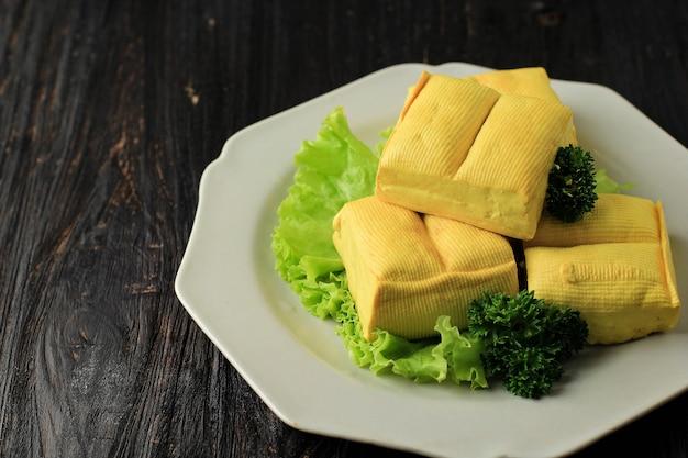 作りたての生豆腐黄色いバンドン豆腐の黒い木製テーブル(タフススレンバン)のクローズアップ。ビーガンヘルシーミールのコンセプト。広告、テキスト、またはレシピ用のコピースペース