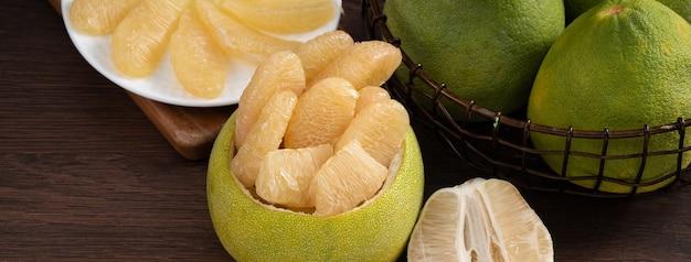 中秋節の果物のための木製のテーブルの背景に新鮮な皮をむいたザボンのクローズアップ。