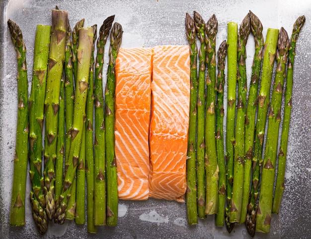 Крупный план свежей сырой зеленой спаржи и сырого филе лосося на противне, сбрызнутом оливковым маслом и приправами. приготовление здорового ужина, подходящего для диеты, хорошего самочувствия, вид сверху, крупный план