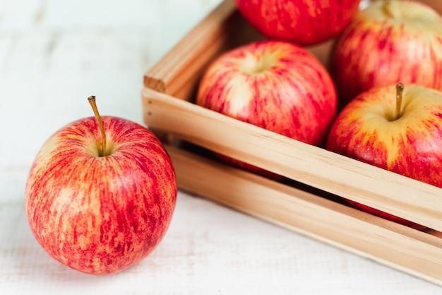 Закройте вверх свежих спелых красных яблок в деревянном ящике.