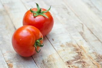 Close-up of fresh, ripe tomatoes on wood background.