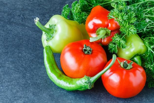 新鮮な完熟トマト、ピーマン、ウッドの背景にパセリのクローズアップ。